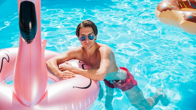 Vorderansichtmann auf flamingoschwimmring Kostenlose Fotos