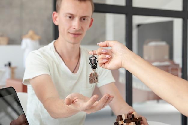 Vorderansichtmann, der die schlüssel für ein neues haus annimmt Kostenlose Fotos