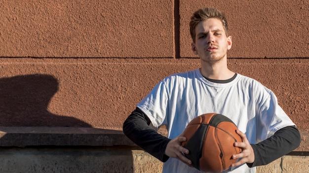 Vorderansichtmann, der einen basketball hält Kostenlose Fotos