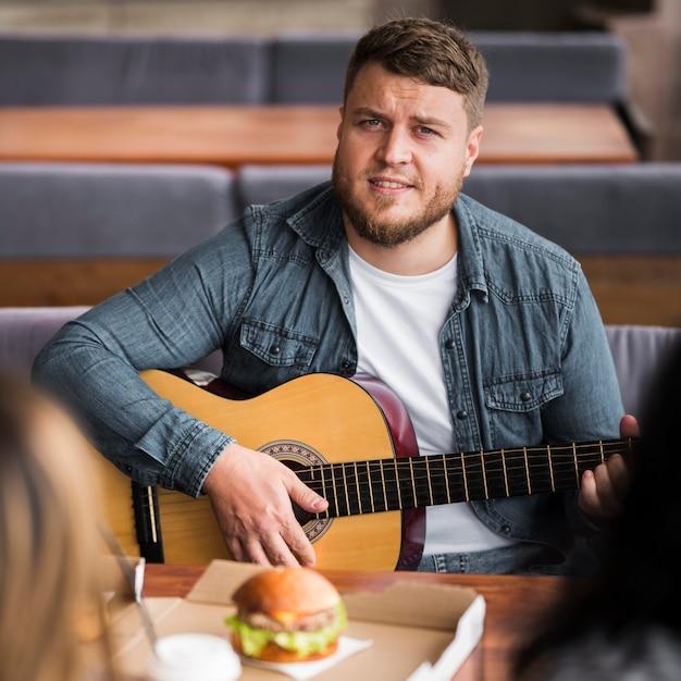 Vorderansichtmann, der gitarre am tisch spielt Kostenlose Fotos