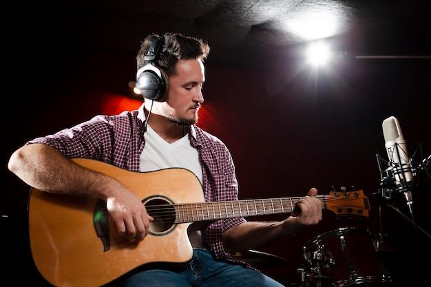 Vorderansichtmann, der gitarre spielt und kopfhörer trägt Kostenlose Fotos