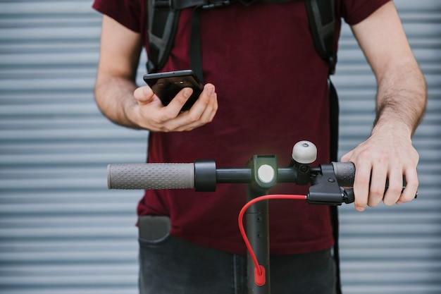 Vorderansichtmann, der telefon auf elektroroller hält Kostenlose Fotos