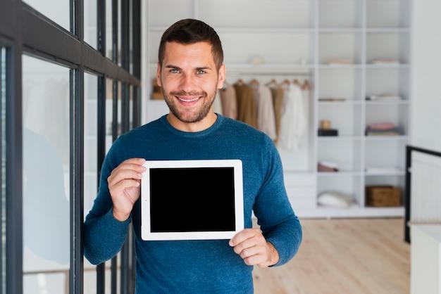 Vorderansichtmann mit der tablette, die sie zur kamera zeigt Kostenlose Fotos