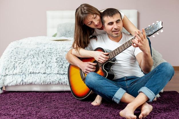Vorderansichtmann und -frau, die gitarre spielen Kostenlose Fotos