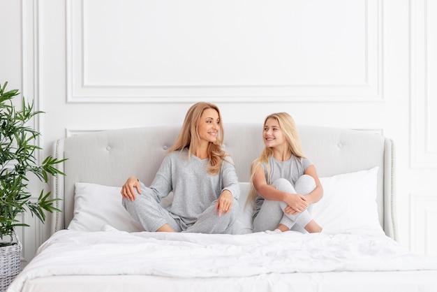 Vorderansichtmutter und -tochter, die im bett sitzen Kostenlose Fotos