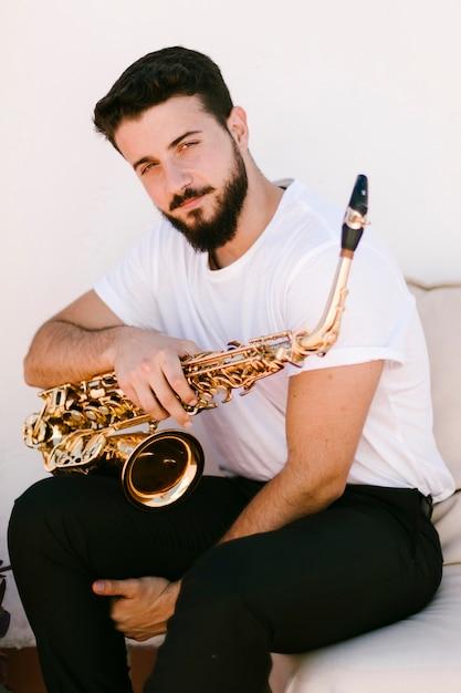 Vorderansichtporträt des mannes aufwerfend mit saxophon Kostenlose Fotos