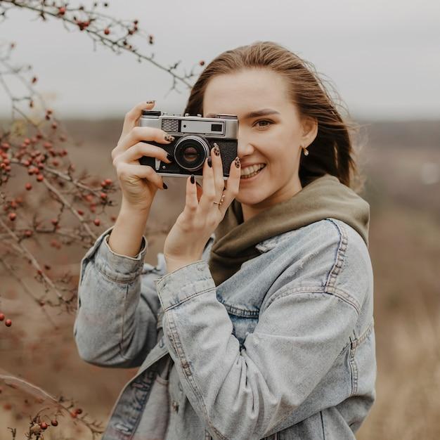 Vorderansichtsmileyfrau, die fotos macht Kostenlose Fotos