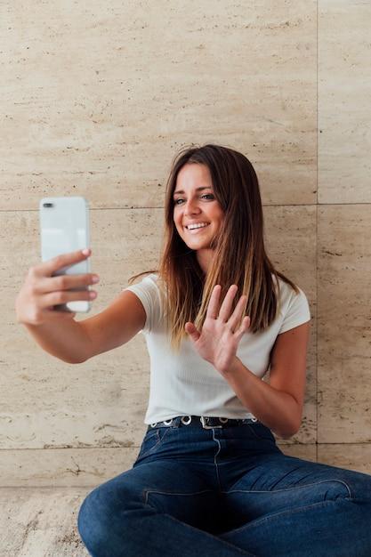 Vorderansichtsmileymädchen, das am telefon wellenartig bewegt Kostenlose Fotos