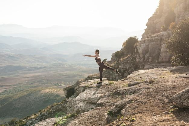 Vorderansichtyoga-balancenhaltung auf berg Kostenlose Fotos