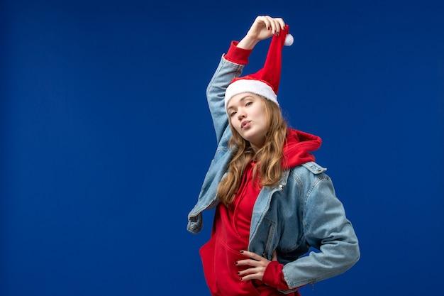 Vordere ansicht junge frau mit roter weihnachtskappe auf blauem hintergrund emotionen weihnachtsfarbe Kostenlose Fotos