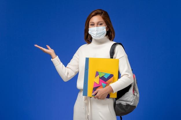 Vordere ansicht junge studentin im weißen trikot mit maske mit tasche und heften an der blauen wand Kostenlose Fotos