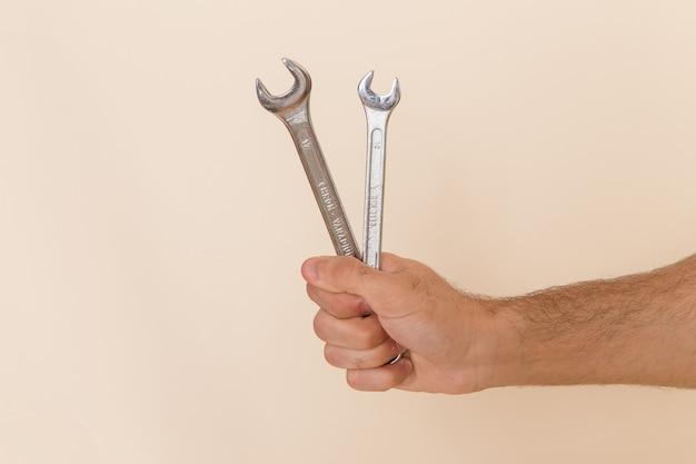 Vordere ansicht silberne werkzeuge halten von männlich auf leichtem schreibtischinstrument werkzeug männlich Kostenlose Fotos