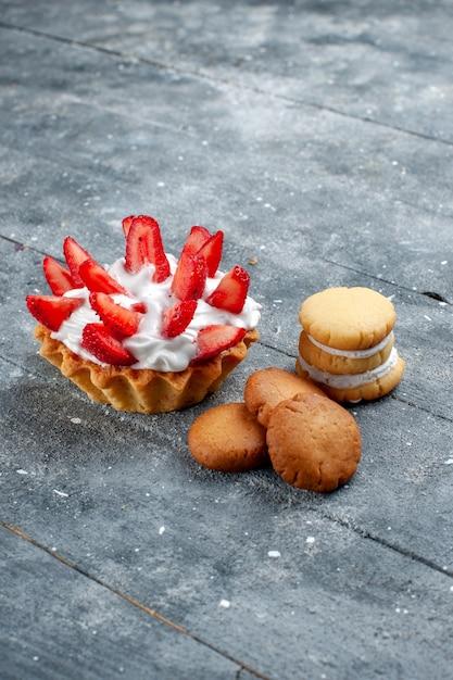 Vordere entfernte ansicht kleiner cremiger kuchen mit geschnittenen erdbeeren und keksen auf grau Kostenlose Fotos