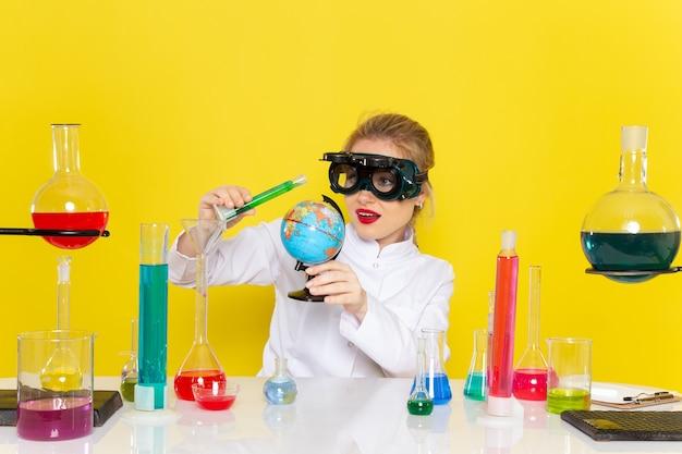 Vordere fernsicht junge chemikerin im weißen anzug mit farbigen lösungen, die mit ihnen mit maske auf gelb arbeiten Kostenlose Fotos