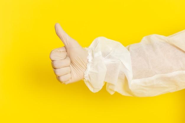 Vordere nahansicht des männlichen wissenschaftlichen arbeiters im speziellen schutzanzug und zeigt wie zeichen auf gelber wand Kostenlose Fotos