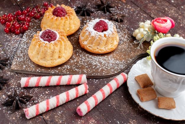 Vordere nahansicht kleine köstliche kuchen mit himbeeren und preiselbeeren zusammen mit stick bonbons kaffee auf holzschreibtisch, kuchen süße frucht backen keks beere Kostenlose Fotos