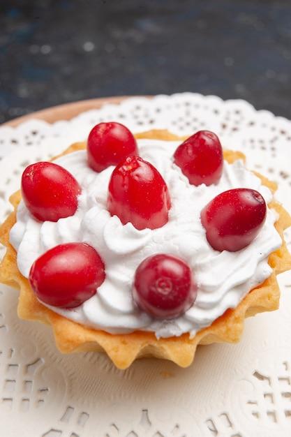 Vordere nahansicht kleiner köstlicher kuchen mit sahne und roten früchten auf der dunklen oberfläche kuchenfruchtkeks süß Kostenlose Fotos