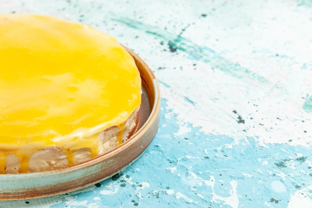 Vordere nahansicht köstlicher kuchen mit gelbem sirup auf hellblauer oberfläche Kostenlose Fotos