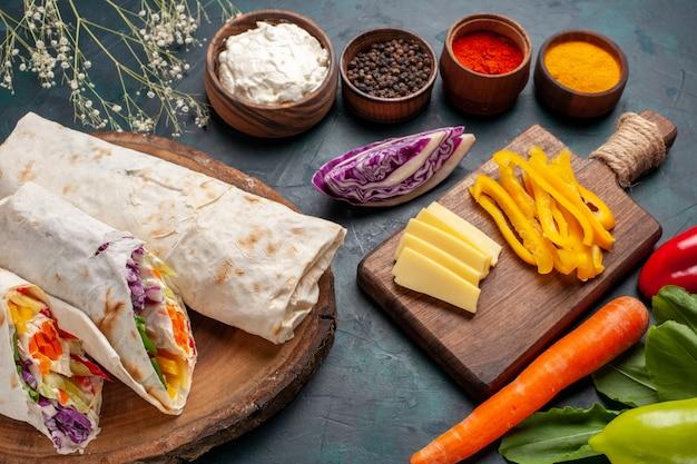 Vordere nahansicht köstliches fleischsandwich ein sandwich aus fleisch am spieß mit gewürzen auf blauem schreibtisch gegrillt Kostenlose Fotos