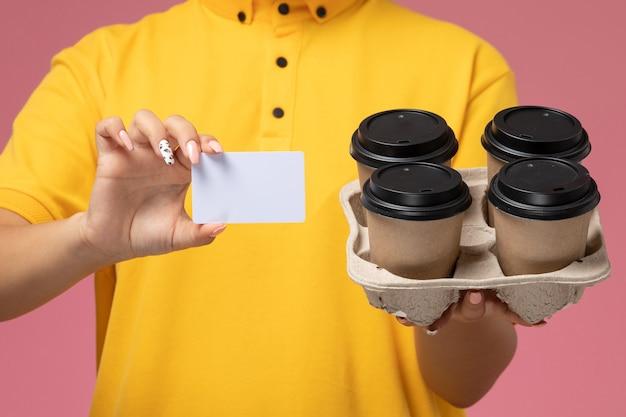 Vordere nahansicht weiblicher kurier in gelbem einheitlichem gelbem umhang, der kaffeetassen mit weißer karte auf rosa hintergrunduniformlieferarbeitsfarbauftrag hält Kostenlose Fotos