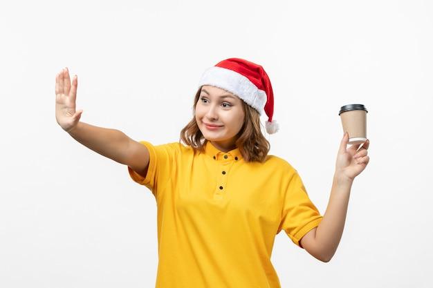 Vorderer blick junger weiblicher kurier mit kaffee auf weißer wanduniformdienstlieferung Kostenlose Fotos