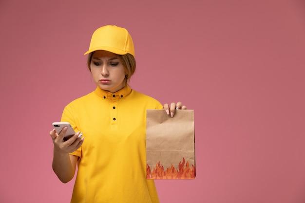 Vorderer blick weiblicher kurier in gelbem einheitlichem gelbem umhang, der lebensmittelverpackung unter verwendung eines telefons auf rosa hintergrunduniformlieferarbeitsfarbauftrag hält Kostenlose Fotos