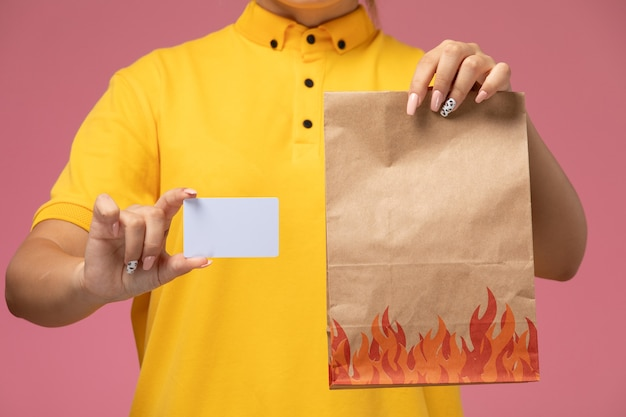 Vorderer blick weiblicher kurier in gelbem einheitlichem gelbem umhang, der weiße karte und lebensmittelpaket auf rosa schreibtischuniformlieferarbeitsfarbauftrag hält Kostenlose Fotos