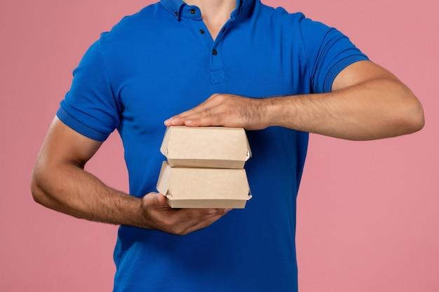 Vorderer nahansicht junger männlicher kurier im blauen uniformumhang, der kleine liefernahrungsmittelpakete an der rosa wand hält, servicemitarbeiter liefert Kostenlose Fotos