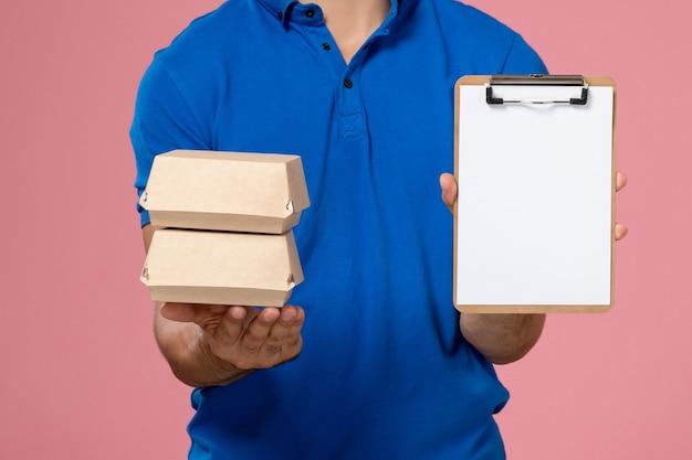 Vorderer nahansicht junger männlicher kurier im blauen uniformumhang, der kleine liefernahrungsmittelpakete mit notizblock auf hellrosa wand hält, einheitlichen service liefert Kostenlose Fotos