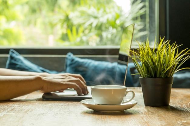 Vorgewählter fokustasse kaffee mit dem geschäftsmann, der auf dem tastaturlaptop schreibt Premium Fotos