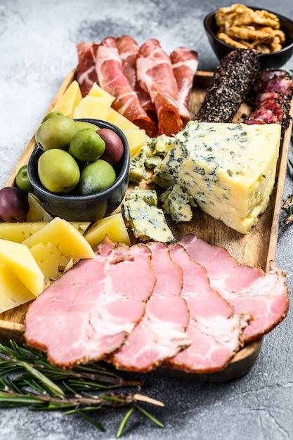 Vorspeise mit verschiedenen antipasti, schneidebrett mit schinken, salami, coppa, käse und oliven. ansicht von oben Premium Fotos