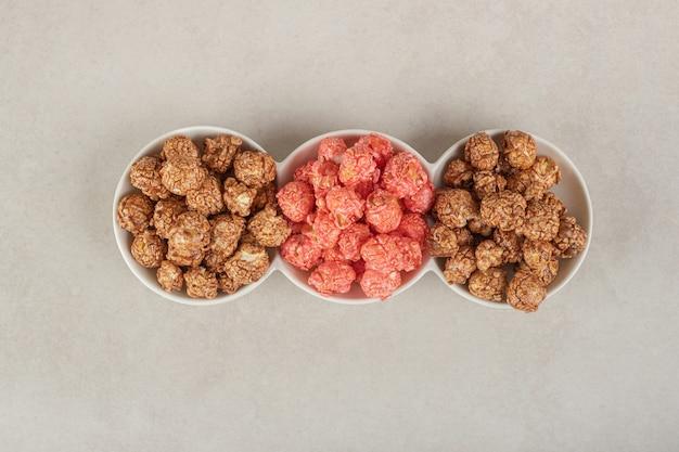Vorspeisenplatte mit verschiedenen popcorn-bonbons auf marmor. Kostenlose Fotos