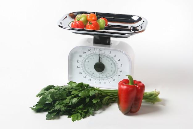 Waage und gemüse, gesundes vegetarisches essen. weißer hintergrund. Premium Fotos