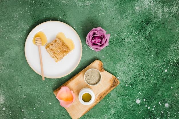 Wabenschöpflöffel; honig; rosenblatt; rhassoul lehm und pulver auf grünem strukturiertem hintergrund Kostenlose Fotos