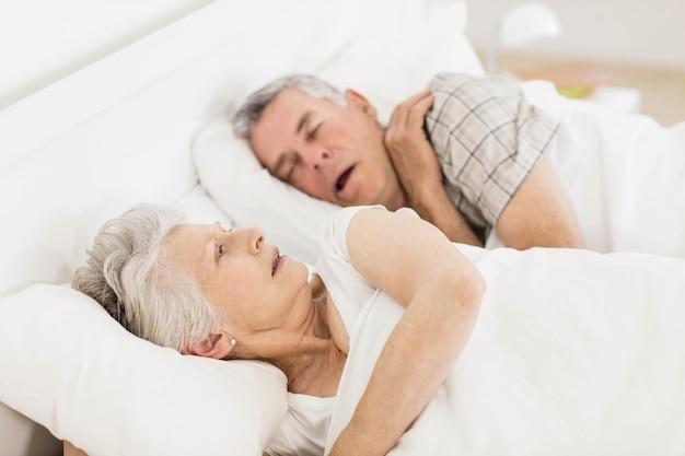 Wachen sie ältere frau im bett auf, während ihr ehemann schnarcht Premium Fotos
