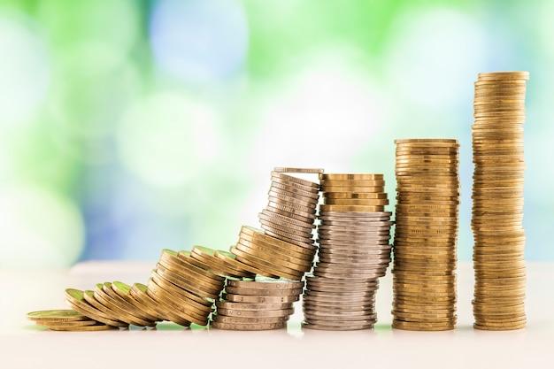 Wachsende münzenstapel mit grünem und blauem funkelndem bokeh. Premium Fotos