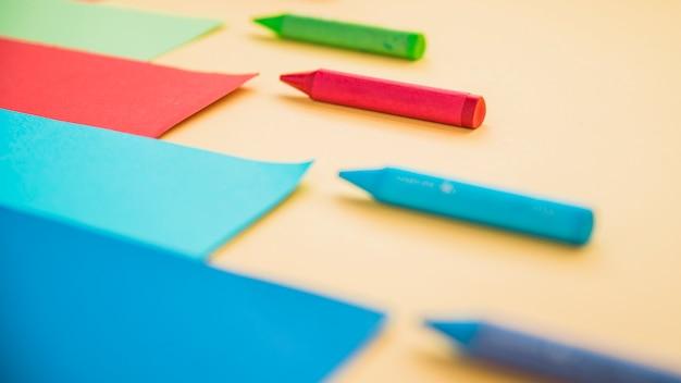 Wachsmalstiftfarbe und kartenpapier in folge angeordnet Kostenlose Fotos