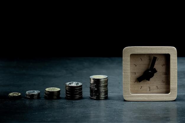 Wachstumsdiagramm vom stapel der münze mit hölzerner uhr Premium Fotos