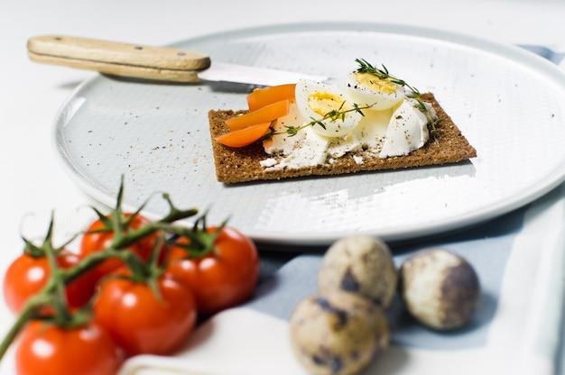 Wachtelei toast. zutaten tomaten, ei, käse, roggenbrot. Premium Fotos