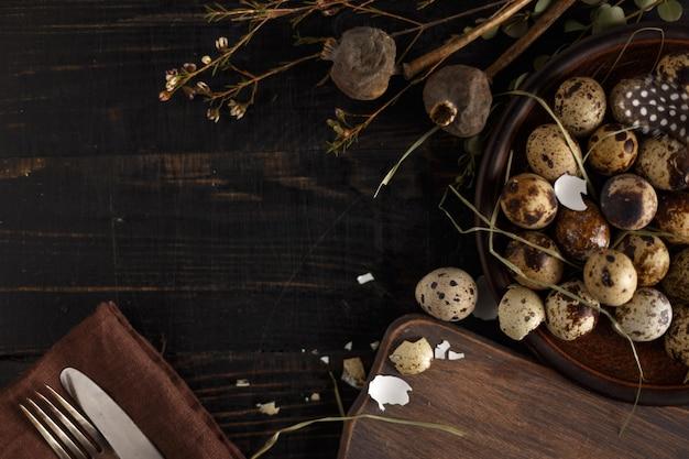 Wachteleier auf einer lehmplatte auf einer dunklen holzoberfläche. Premium Fotos