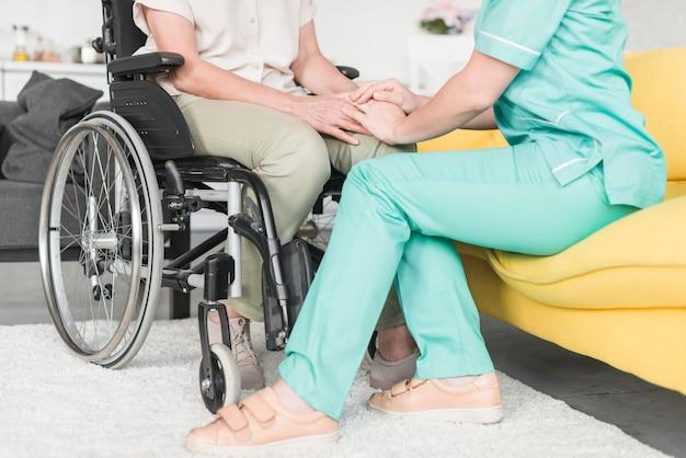 Wärter, der hand des weiblichen patienten sitzt auf rollstuhl hält Kostenlose Fotos