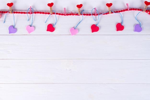 Wäscheklammern mit roten herzen auf einem band auf einem weißen hölzernen hintergrund. valentinstag Premium Fotos
