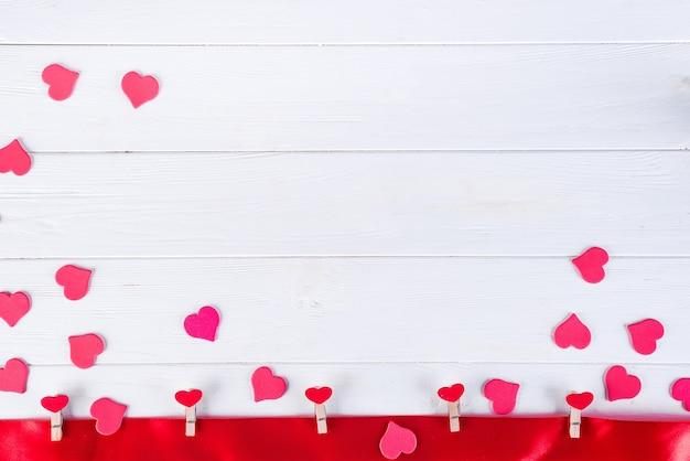 Wäscheklammern mit roten herzen auf einem roten band auf einem weißen hölzernen hintergrund von valentine day Premium Fotos