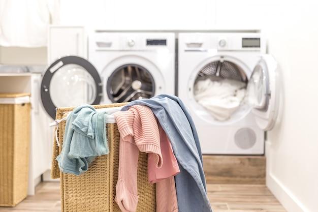 Wäschekorb mit schmutziger kleidung mit wasch- und trockenmaschinen auf dem hintergrund Premium Fotos