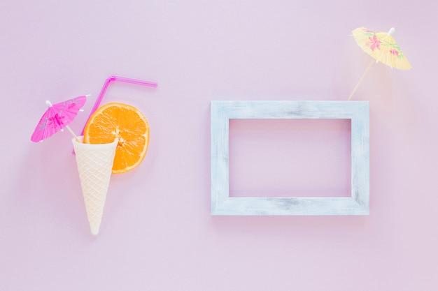 Waffelkegel mit orange, stroh und regenschirm nahe rahmen Kostenlose Fotos