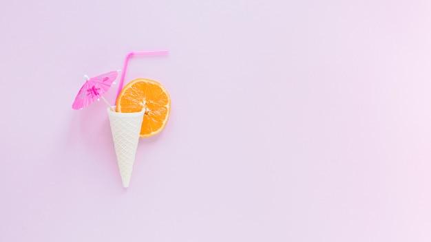 Waffelkegel mit orange, stroh und regenschirm Kostenlose Fotos