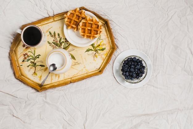 Waffeln; milchglas; kaffeetasse und blaubeereschüssel auf weißer zerknitterter tischdecke Kostenlose Fotos