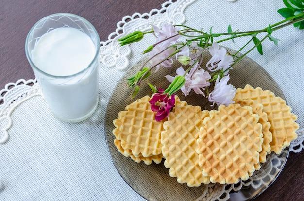 Waffeln mit aquilegia-blüten und einem glas milch Premium Fotos