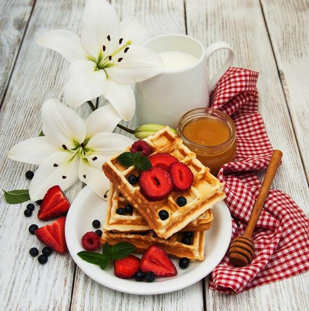 Waffeln mit erdbeeren, heidelbeeren und kaffee Premium Fotos