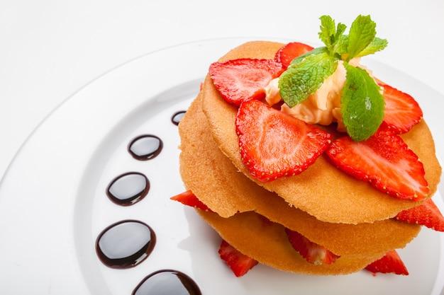 Waffeln mit karamellsoße, schlagsahne und erdbeeren lokalisiert auf weißem hintergrund Premium Fotos